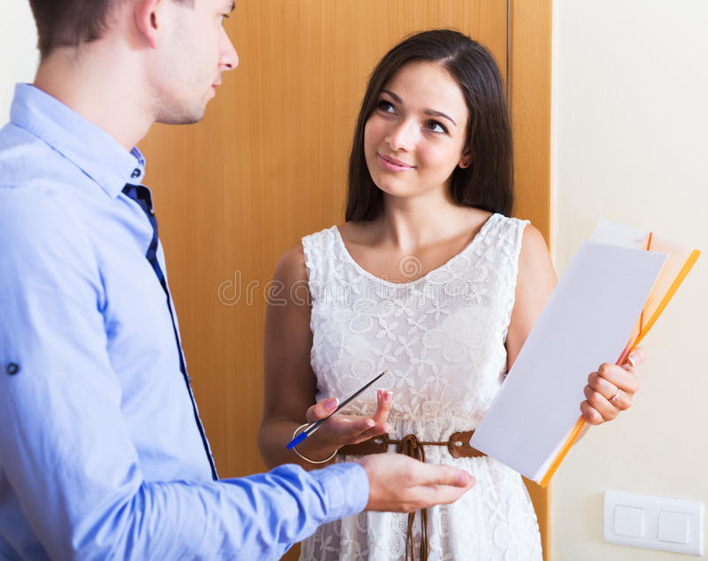 Seller showing documents indoors. Positive seller showing documents and making good offer indoors royalty free stock image