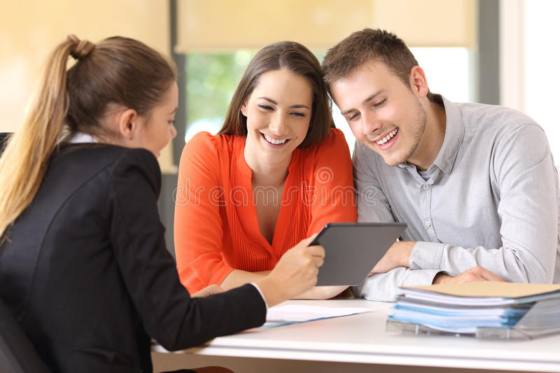 Seller showing on line product to the customers. Seller showing on line products with a tablet to the customers in a desktop at office stock photo