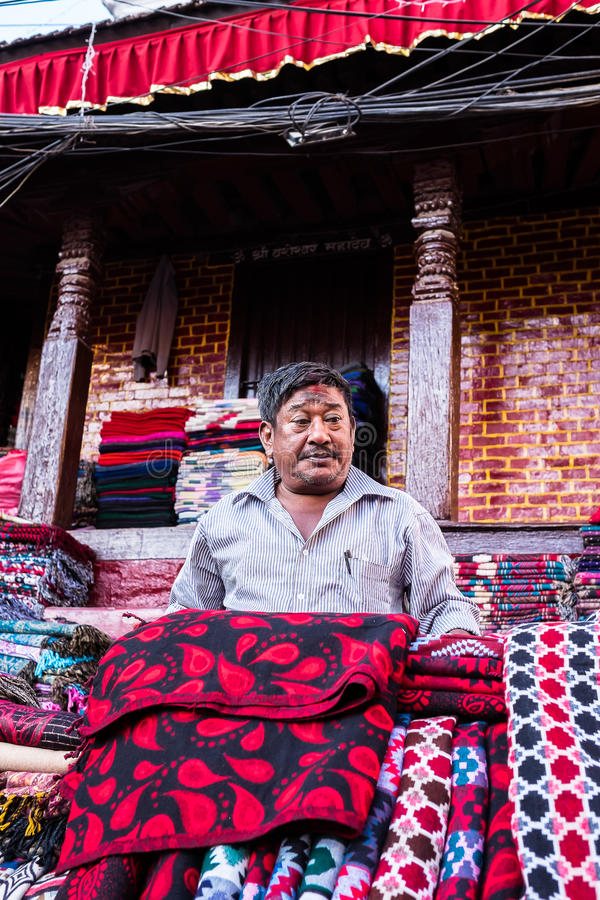 A seller showing Tibetan yak wool blankets or scarfs to customers on the market in Thamel district stock photos