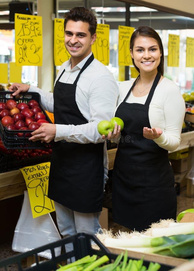 Sellers offering seasonal sweet apples in grocery stock image