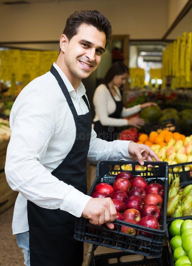 Sellers offering seasonal sweet apples in grocery stock images