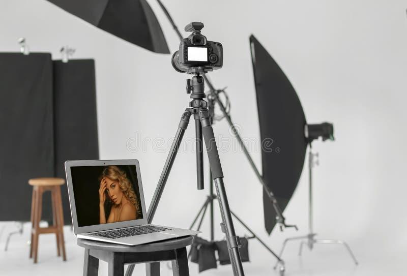 Selles avec l'ordinateur portable et la caméra sur le trépied dans le studio moderne de photo image stock