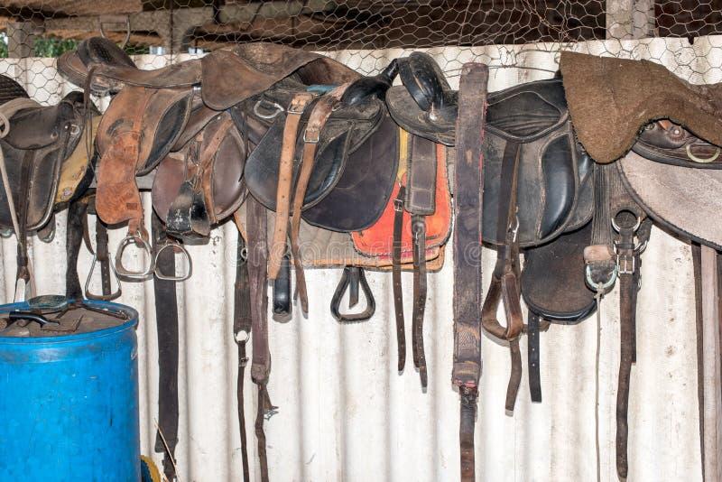 Selles de cheval dans la grange images libres de droits