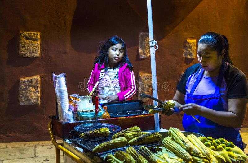 Selling Corn on the Street. A woman and daughter sell cooked corn at a street stall in Oaxaca, Mexico royalty free stock image