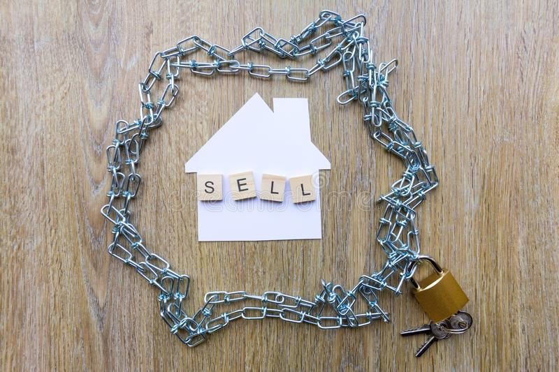 Chain surrounding a house with the word sell. Selling and debt concept - chain surrounding a house with the word sell royalty free stock photos
