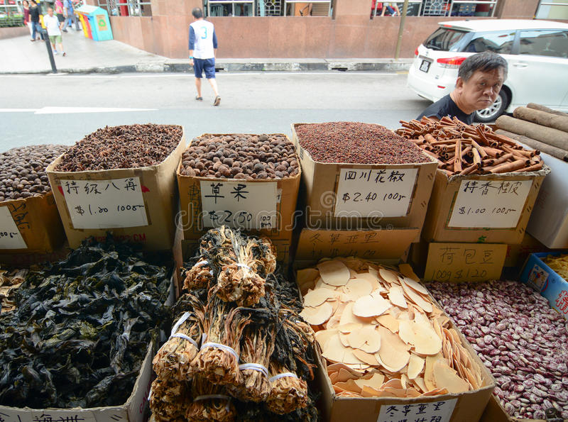 Selling dried herbal and dried food at Chinatown. Singapore - Oct 3, 2015. A man buying dried herbal and dried food at Chinatown of Singapore. It is a stock photography