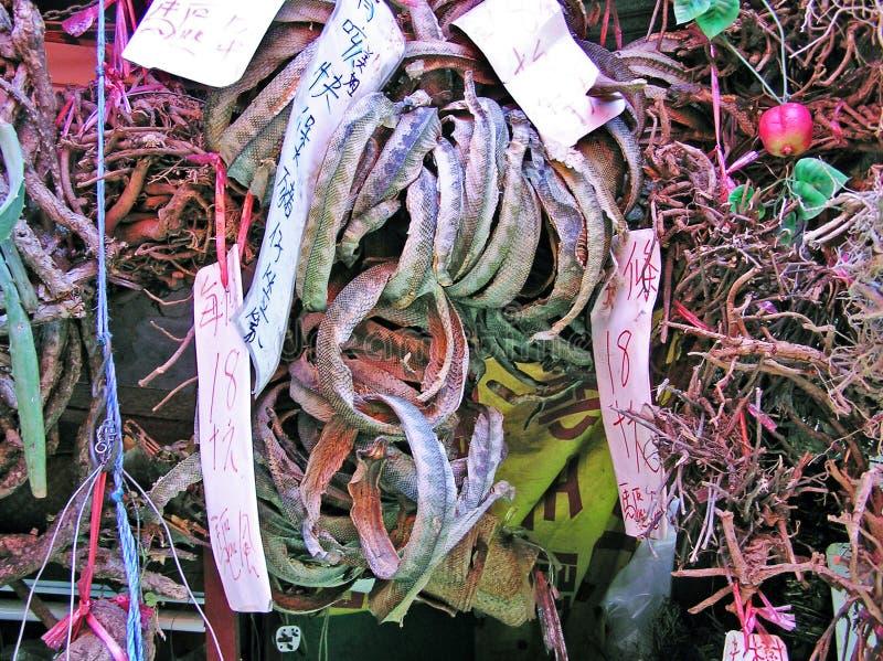 Selling dried snake skins at a street market in Hong Kong, China royalty free stock photos