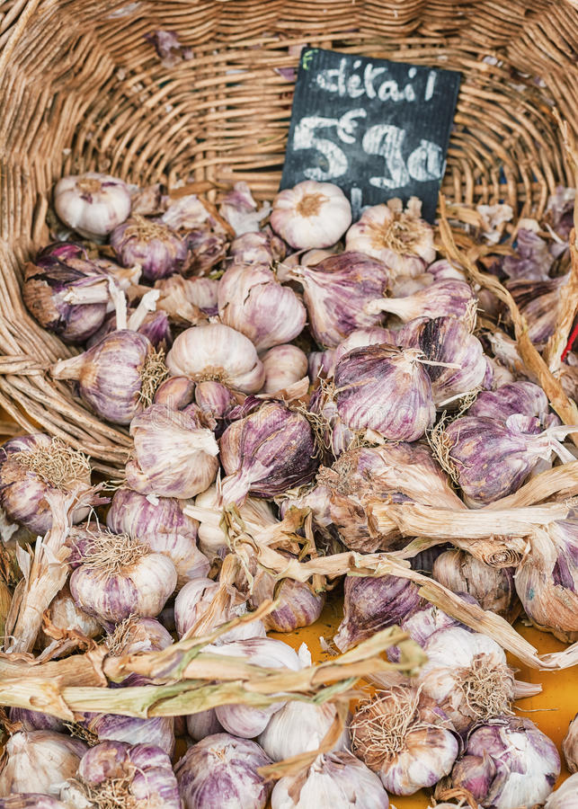 Selling garlic on the market in France. Garlic in a basket with a price tag royalty free stock photo