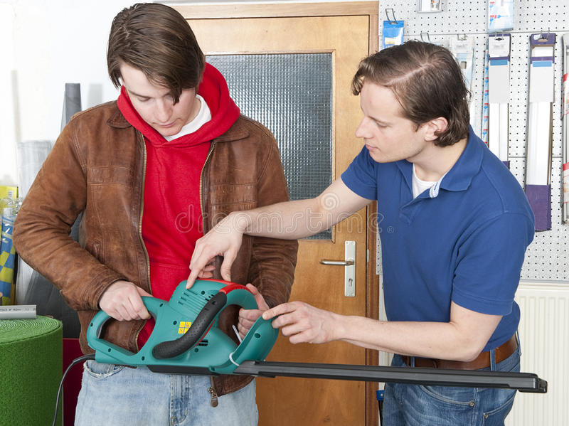 Selling hedgeshears. Salesman at a hardware store demonstrating and selling hedge shears to a customer stock image
