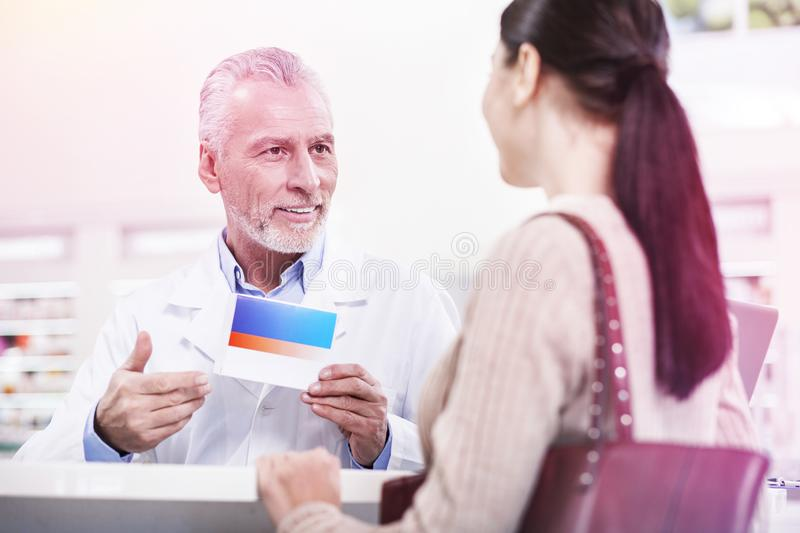 Confident worker of the pharmacy offering new medication to a woman. Selling medication. Confident worker of the pharmacy offering new medication to a curious royalty free stock image