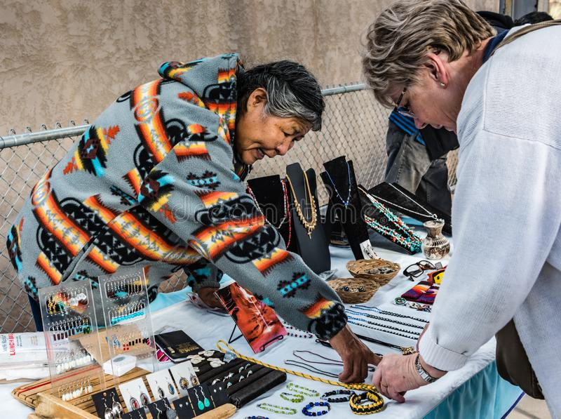 Selling Navajo Jewelry In Albuquerque. Albuquerque, New Mexico / USA / April 1, 2016: Native American woman selling hand crafted jewelry at the train station royalty free stock photography