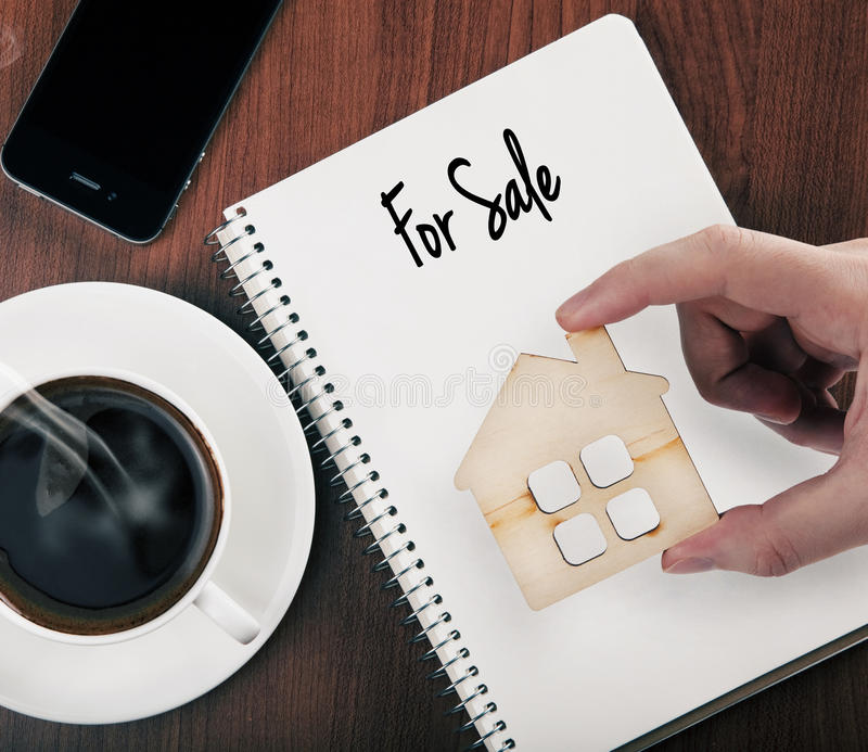 Selling of real estate. Hand holding wooden home as symbol of selling of real estate stock images
