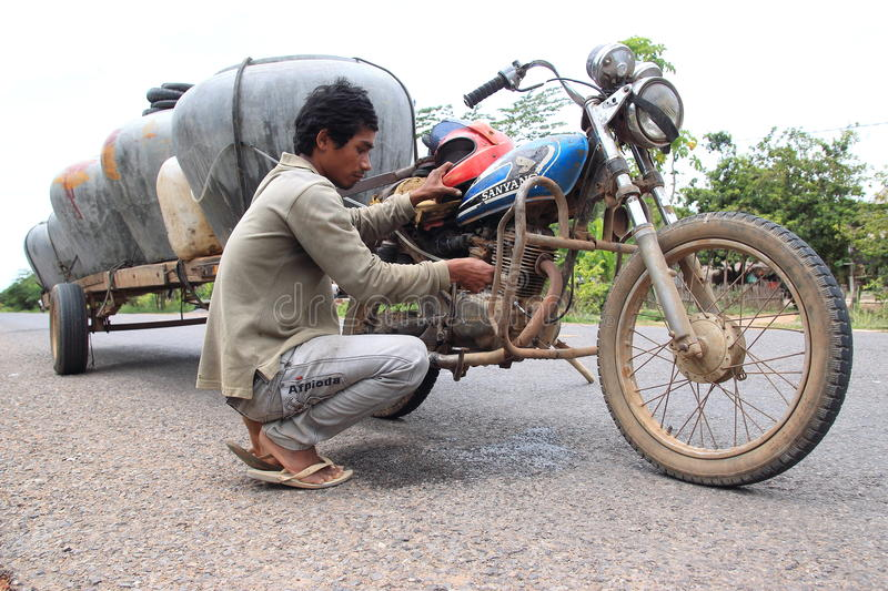Selling water barrels from a motorbike in Cambodia stock photos