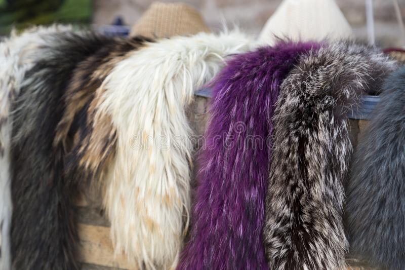 Selling women`s natural fur scarf. Fur scarf store. Selling women`s natural fur scarf at outdoors. Trading with fur shawls royalty free stock photography