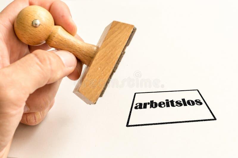 Selo em um fundo branco sobre o desemprego com a palavra alemão para desempregados foto de stock royalty free