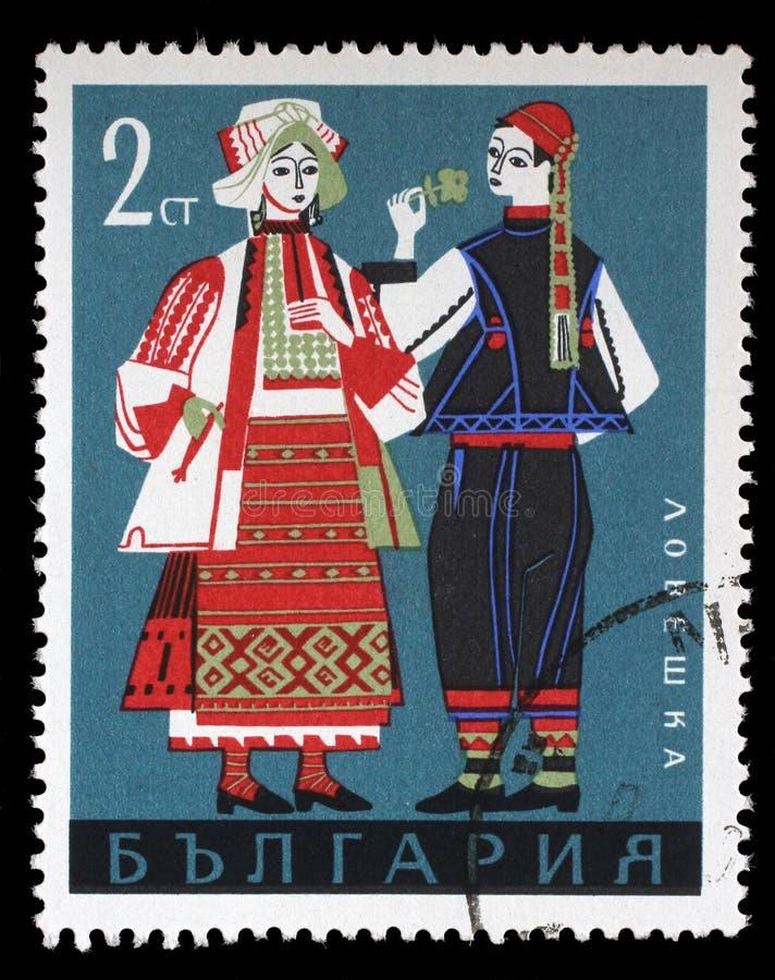 Selo impresso em Bulgária, mostras homem e mulher em trajes nacionais búlgaros da região de Lovech fotografia de stock