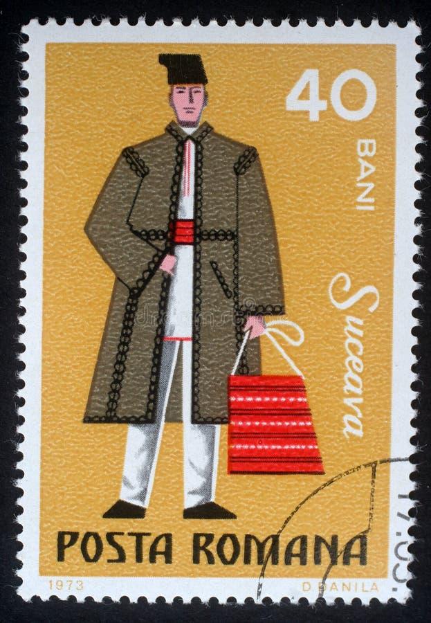 Selo impresso em Romênia, mostras o vestido tradicional dos homens na região Suceava fotografia de stock