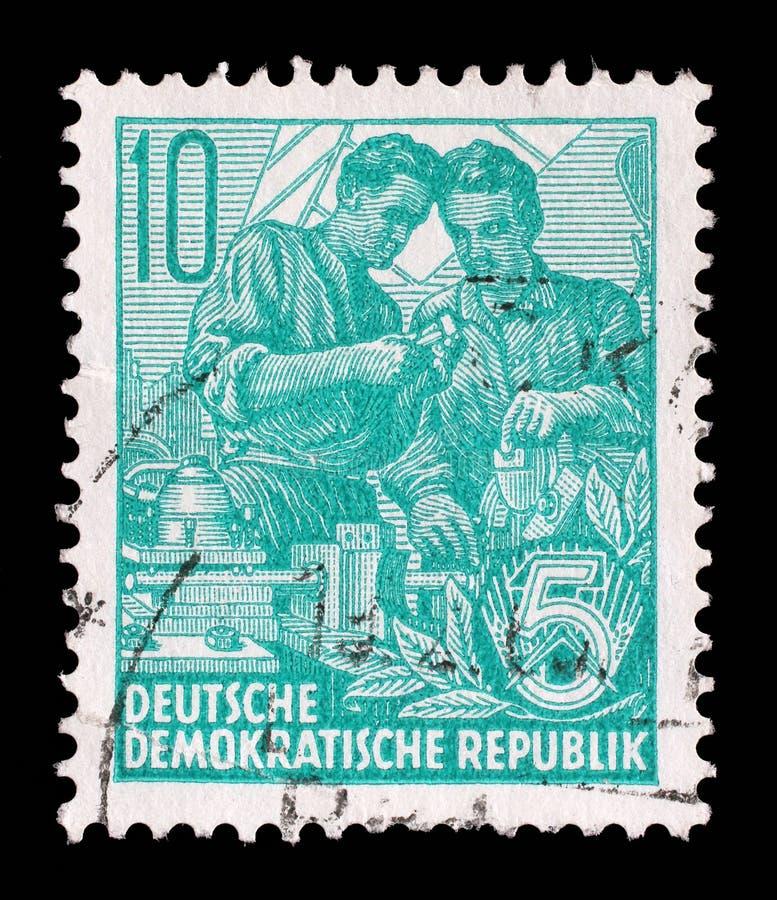 Selo impresso no GDR, mostras dois trabalhadores fotografia de stock royalty free