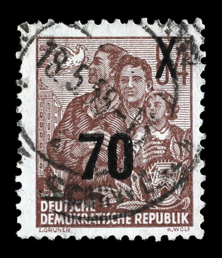 Selo impresso no GDR, mostras uma família fotos de stock royalty free