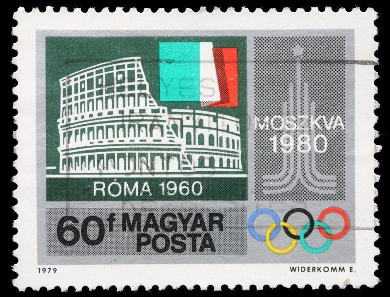 Selo impresso por Hungria, mostras Colosseum, Roma, bandeira italiana, emblema de Moscou imagem de stock royalty free