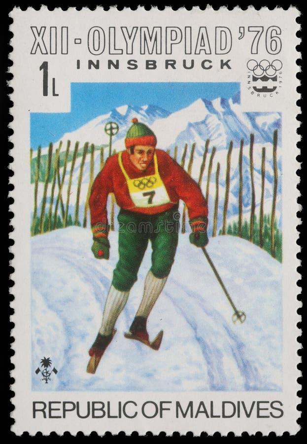 Selo impresso por Maldivas, esqui alpino das mostras nos Olympics de inverno em Innsbruck fotografia de stock