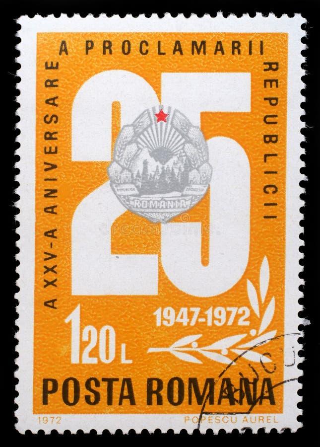Selo impresso por Romênia, pelas mostras 25 e pelo emblema nacional, aniversário 25 da edição da república foto de stock royalty free