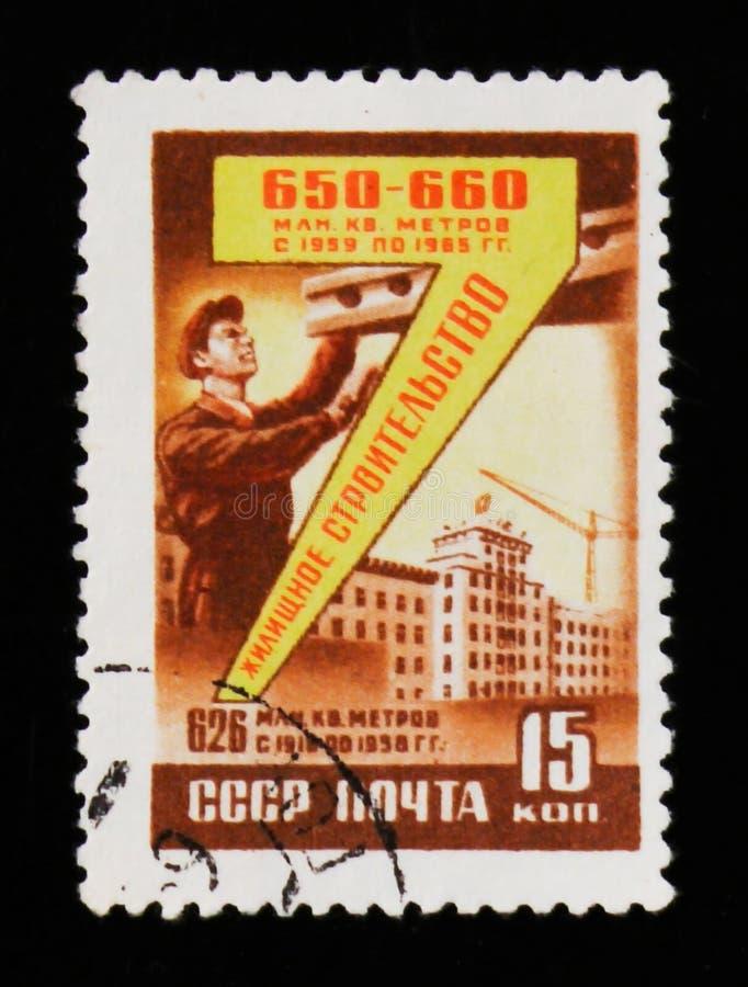 Selo postal devotado à refinaria de petróleo, homem das mostras pela máquina, cerca de 1958 fotos de stock royalty free