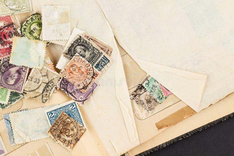 Selos postais fracos do vintage no livro fotos de stock royalty free