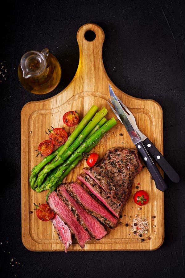Seltenes Rindfleisch des saftigen Steaks mit Gewürzen auf einem hölzernen Brett und schmückt vom Spargel stockfoto