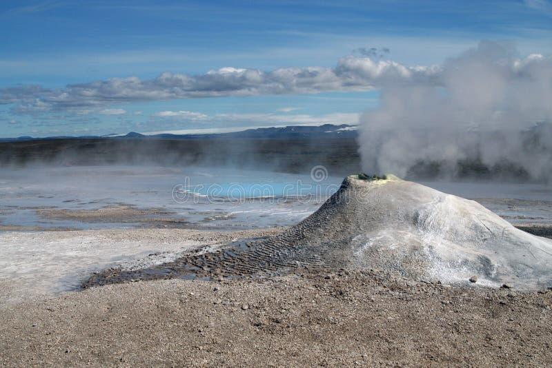 Seltun/Krysuvik Krýsuvík: O mini vulcão como a fumarola emite-se o gás sulfúrico com cozinhar a associação natural azul quente no imagem de stock