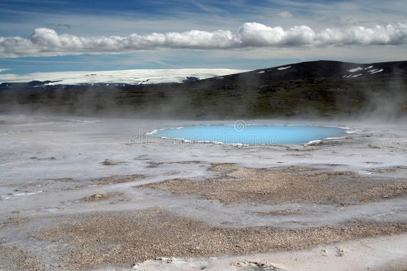 Seltun / Krysuvik Krýsuvík: Steaming geothermal valley with natural blue pool and snowcapped mountain. Steaming geothermal valley with natural blue pool royalty free stock photos