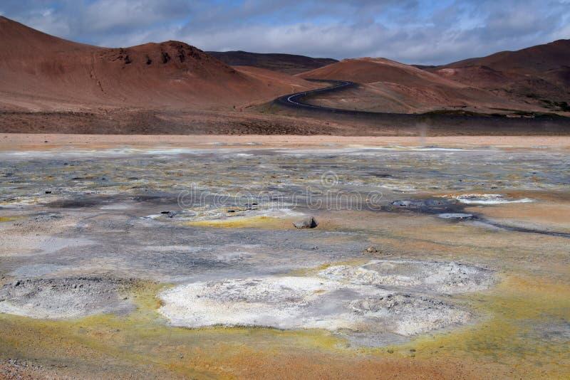 Seltun/Krysuvik Krýsuvík: Väg till och med röda kullar som leder för att gulna, och den vita geotermiska dalen royaltyfria foton