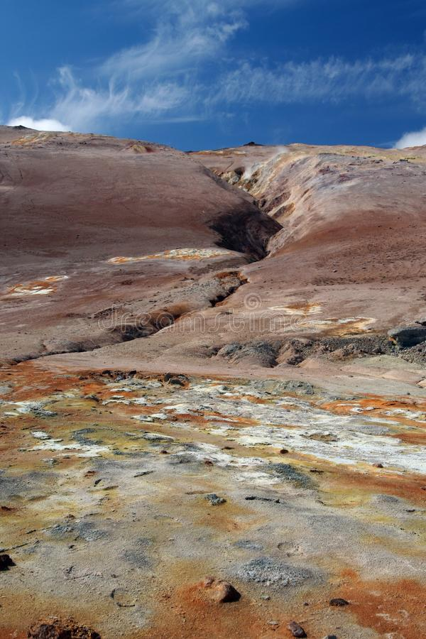 Seltun / Krysuvik Krýsuvík: View over yellow, orange and white geothermal field on fissure of red hill contrasting with blue. View over yellow, orange and stock image