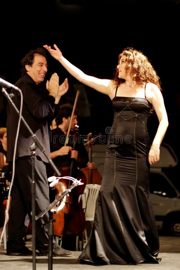 Selva Erdener with conductor Naci Ozguc. Members of the Maltepe Symphonic Orchestra perform live at Maltepe open air stage on July 11, 2010 in Istanbul. Soprano royalty free stock images