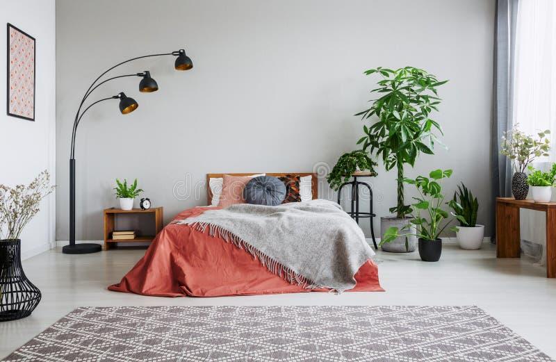 Selva urbana en dormitorio con la cama matrimonial, la lámpara y la alfombra foto de archivo