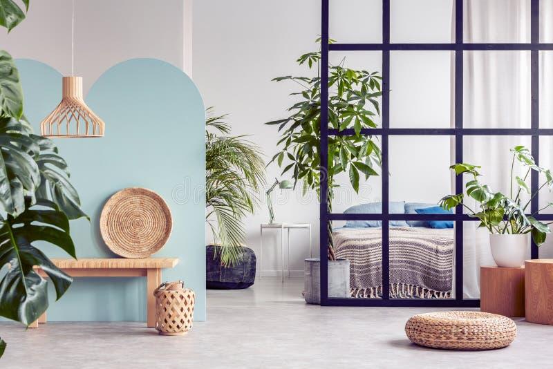Selva urbana en interior de moda del apartamento del plan abierto con la pared de los parteluces foto de archivo