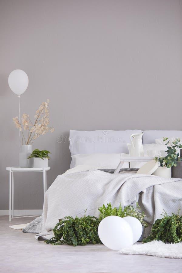 Selva urbana y globos blancos en el dormitorio elegante interior con el espacio de la cama gigante y de la copia en la pared gris imagenes de archivo