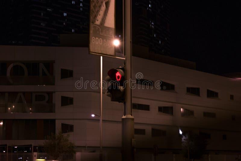 Semáforo rojo en la noche, para los peatones en la calle - señal de peligro de no cruzar el camino imagen de archivo libre de regalías