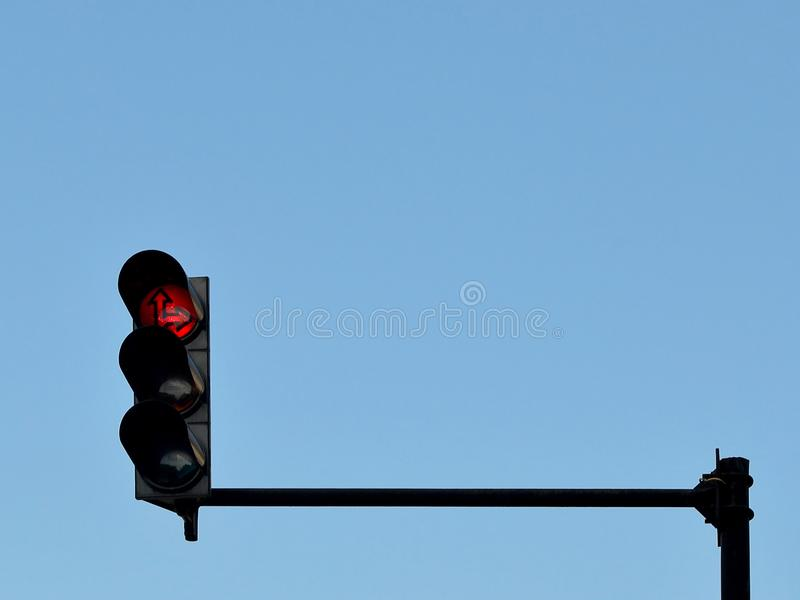 Semáforo rojo instalado en un polo sobre un camino, contra un cielo azul imagen de archivo libre de regalías