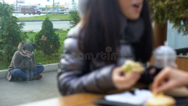 Sem abrigo com fome que sentam-se na rua fora do restaurante, fêmea comendo o café do almoço fotos de stock