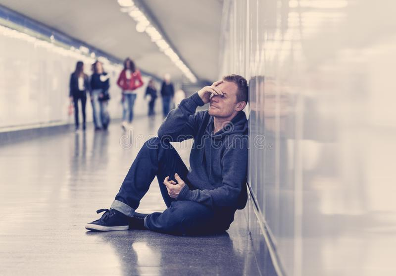 Sem abrigo de grito desempregados miseráveis do viciado em drogas do homem novo no esforço da depressão que senta-se na vista à t imagens de stock