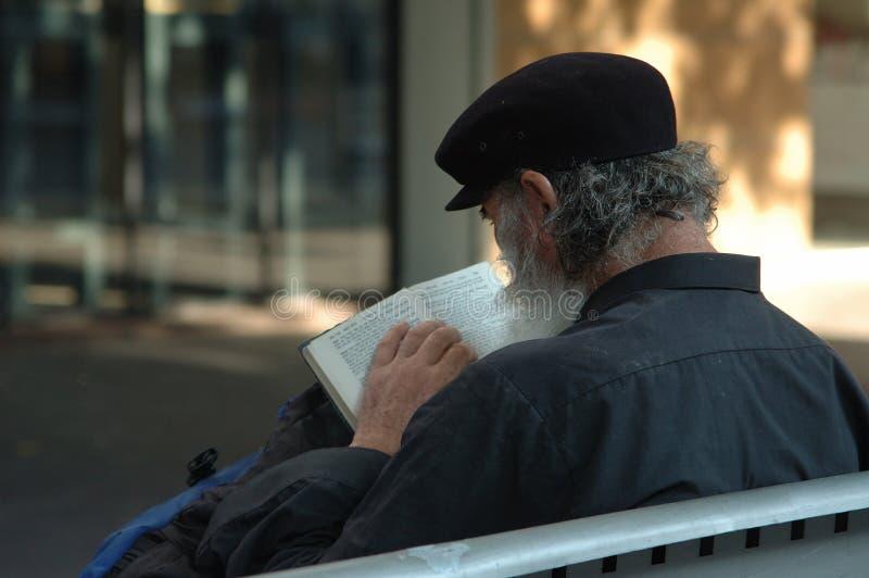 Sem abrigo que lêem a Bíblia foto de stock royalty free