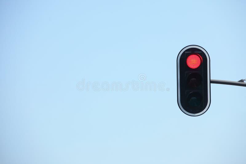 Semafori rossi contro gli ambiti di provenienza del cielo blu immagini stock