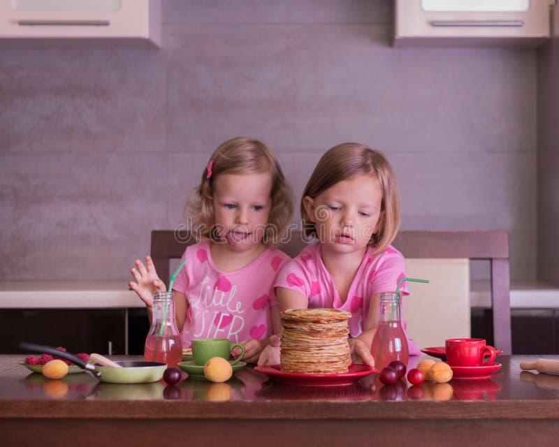Semana de la crepe Las niñas (hermanas) comen las crepes imágenes de archivo libres de regalías