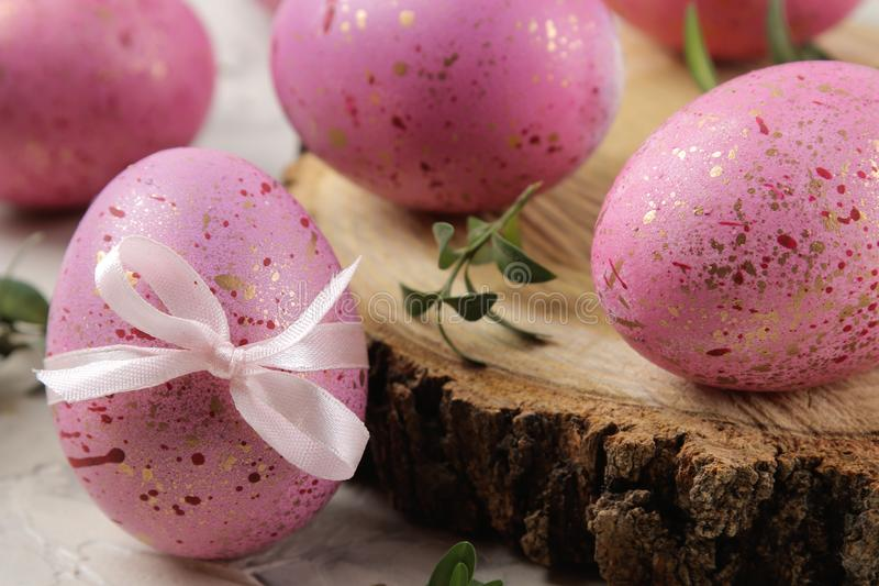 Semana Santa Huevos de Pascua rosados en un soporte de madera en un fondo del cemento ligero Pascua feliz holidays Primer imagen de archivo
