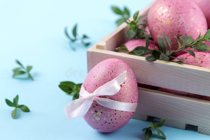 Semana Santa Huevos de Pascua rosados en una caja en un fondo azul de moda Pascua feliz holidays Primer fotos de archivo libres de regalías