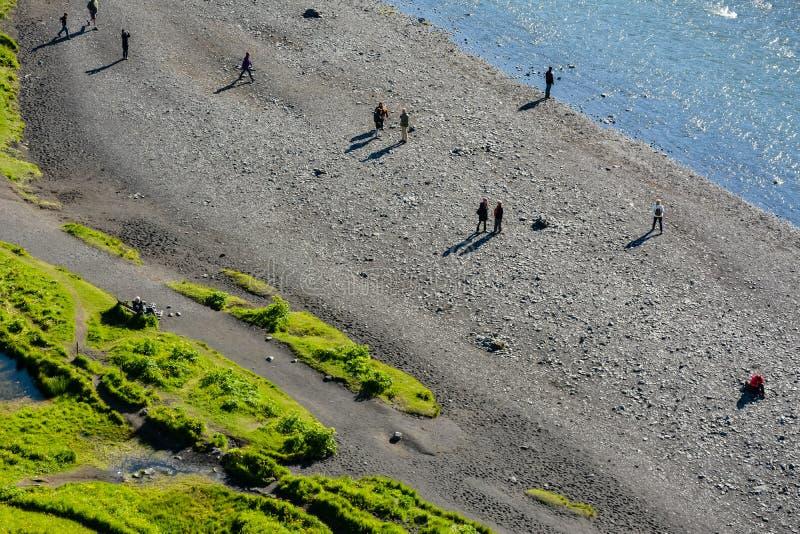Semblant le bon bas sur des personnes par la rivière de Skogar, près de Skogafoss photos stock