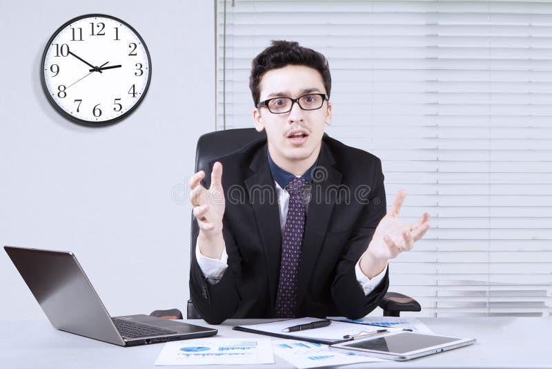 Sembler d'homme d'affaires confus avec le graphique financier photographie stock
