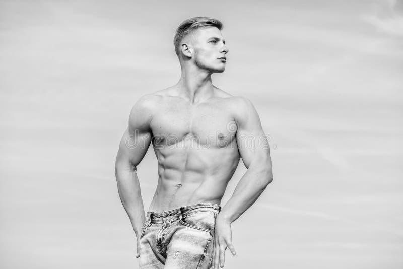 Sembler masculin musculaire de type s?r Fond ext?rieur de ciel bleu de support nu musculaire sexy de torse d'homme Homme musculai photo libre de droits