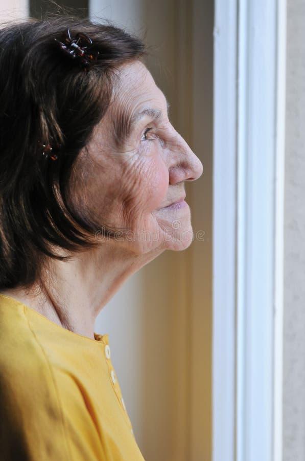 sembrare la donna maggiore della finestra di solitudine fotografia stock libera da diritti
